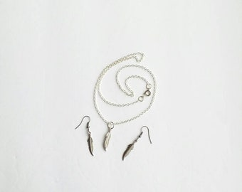Sterling silver earrings and necklace with a feather pendant.
