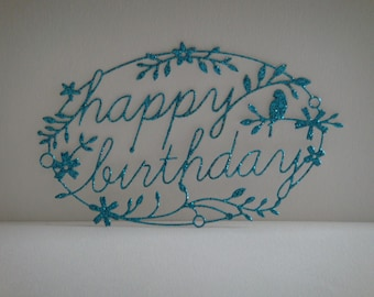 """Oval cut """"Happy Birthday"""" blue glitter with a bird and flowers"""
