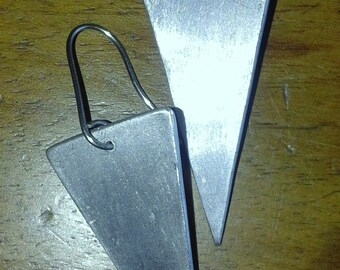 Graphic triangular earrings in brass or aluminium. Minimal
