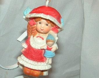 Holly Hobby holding a Doll Christmas Ornament by Carlton