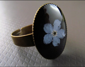 Forget-me-not flower ring on a black background