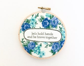 Wall art. Repurposed fabric embroidery hoop. Home decor. Original quote. Holds hands. Brave. Together. Flowers. Floral. Textile art. Words