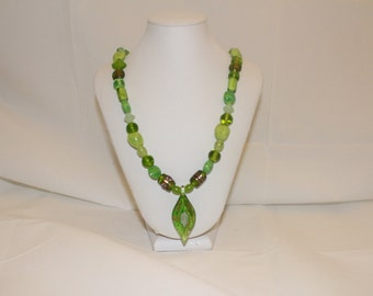 """24"""" green glass beads with gold tone texture.  Pendant 2"""" with gold embellishment."""