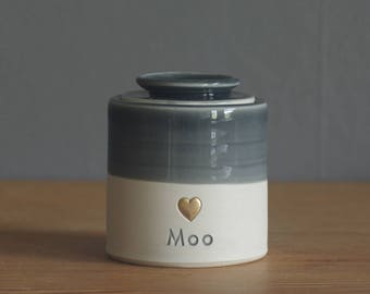 custom urn. gold infilled stamp with ceramic lid, straight shaped urn with custom stamp. modern simple urn for ashes. slate grey urn shown