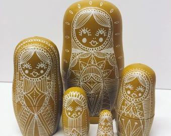Mustard yellow nesting dolls, matryoshka dolls in dolls
