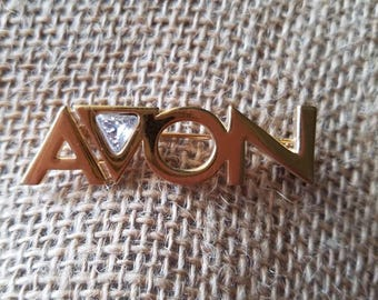 Vintage gold tone AVON brooch wirh faux Diamond in the letter V, like new