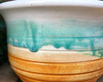 Small planter with white glaze and cerluean accent. Rutile wash on the bottom.
