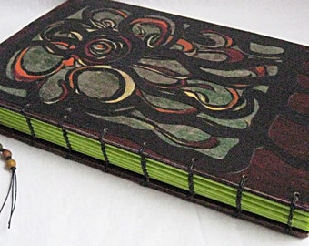Journal with coptic binding in deep shades of red and green with lime green accent on binding and multicolor bead dangle
