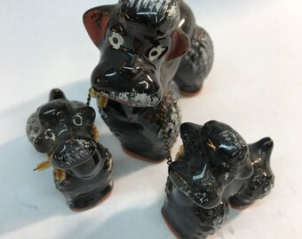 Black poodle statues mother and puppies