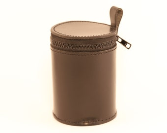 Round container in real leather around 12 cm. high.