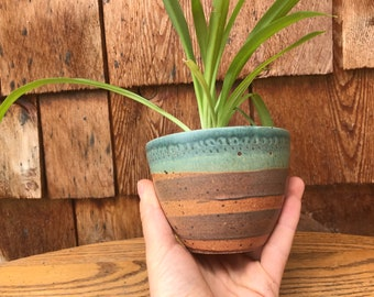 turquoise and orange striped ceramic planter with drainage hole