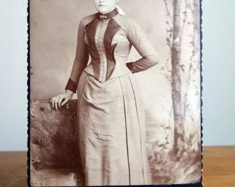 Vintage 1900's photograph postcard of a beautiful very young woman in a very detailed buttoned up Victorian dress