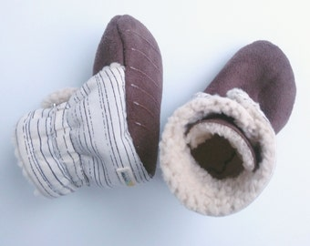 Off-white baby booties with black line design. Gender neutral, perfect for a boy or girl. Black and white.