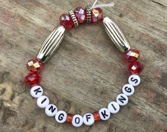 "Sparkly red ""King of Kings"" stretch bracelet with metallic accents"
