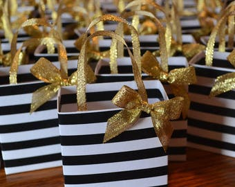 Black and white stripe party favor bag with gold bow and handles,