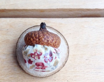 Pin with acorn mounted on wood