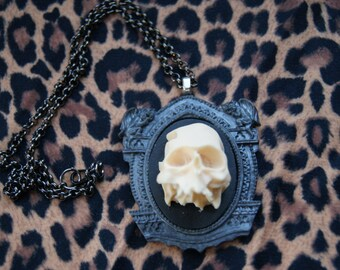 3D skull necklace set on a grey gothic frame, with grotesques.