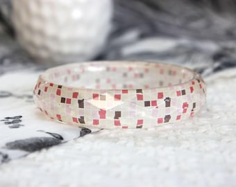 Facetted resin bangle with embedded geometric art pattern