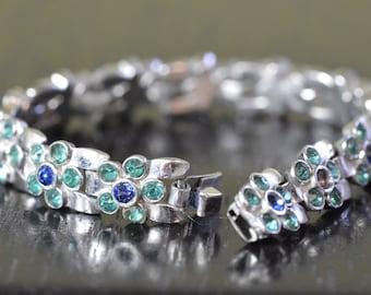 Rhinestone rosettes set in silver bracelet