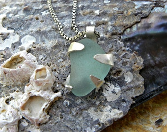 Genuine sea foam sea glass held by knobby sterling starfish pendant necklace