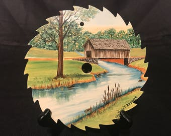 Hand Painted and Sealed Saw Blade with Cover Bridge by Stream Painting Signed by June Brewer 1986