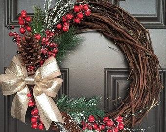 Rustic Christmas wreath with gold bow, red berries, greenery and pinecones