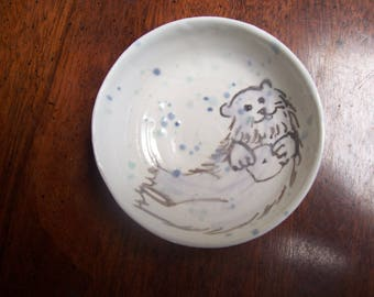 Baby Sea Otter floating in a little bowl