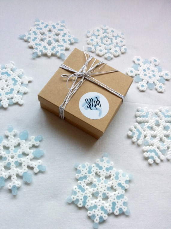 A 7-piece set of pixelated Christmas ornaments made out of white and blue glow-in-the-dark Hama Midi beads