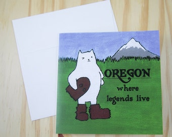 """CARD: """"Oregon Cat"""" featuring a winking cat in a Sasquatch or Bigfoot costume, by Mt. Hood"""