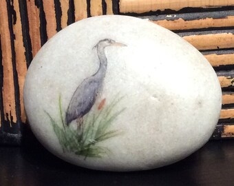 Heron on a natural polished river stone.