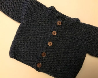 Chaquetita of charcoal grey wool with ochre buttons.