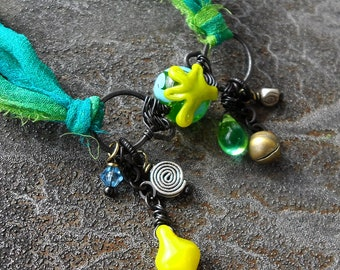 Bittergreen Starshine lampwork bead infinity dangle necklace in lime green and aqua on recycled sari silk