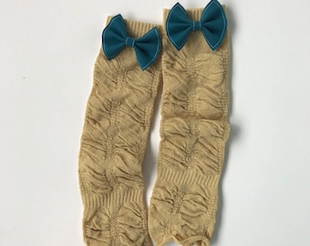 Gold sparkly leg wamers with ruffle and bows