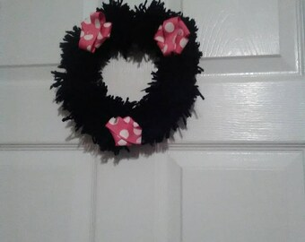 Black pom pom wreath with pink and white ribbon