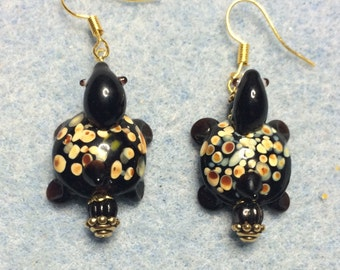 Spotted black lampwork turtle bead earrings adorned with black Czech glass beads.