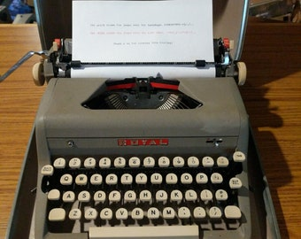 1957 Royal Quiet De Luxe portable typewriter with case, brush, and key to lock the case