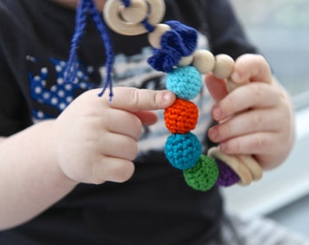 Teething toy rattle with crochet wooden beads and 3 wooden rings. Lilac, teal, green, orange, aqua, blue.