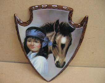 Indian boy with his horse on an arrowhead plaque.