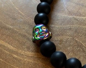 Black Rainbow Buddha: an elastic beaded bracelet with a buddha head, rainbow hematite, and matte black onyx. Both semi precious stones.
