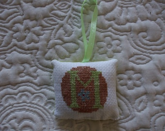 Pillows with letter M embroidered in cross stitch