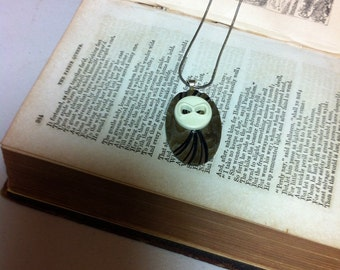 Vintage button necklace resembling an owl