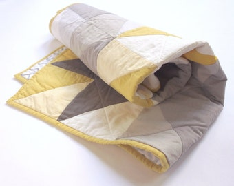 Baby quilt with modern design. Grey, gold and white.