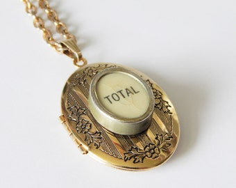 "Vintage cash register key locket necklace, ""TOTAL"" on oval white key, shiny gold toned floral patterned large oval locket with chain"