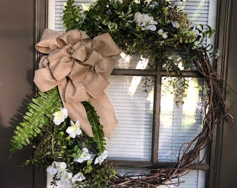 Natural grapevine wreath with greenery and and cream natural colored flowers.