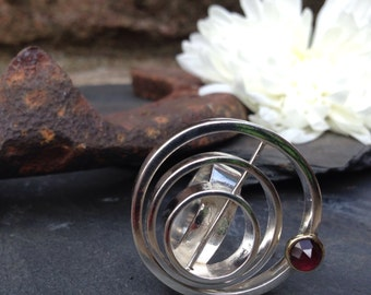 Handmade silver puzzle ring with 18 ct gold setting the red garnet stone.