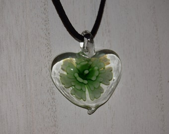 Heart shaped glass pendant with a green floral pattern