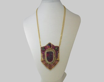 The pendant is embroidered around a Eudyalite