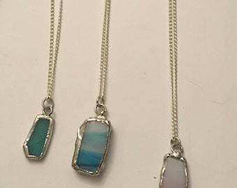 Coloured beach glass pendants .