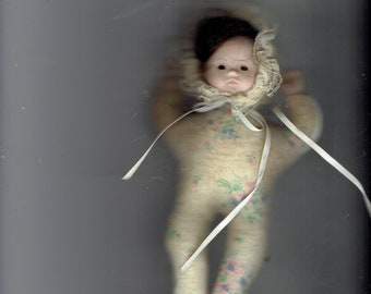 this small porcelain head cloth body doll has been in storage and will need to be cleaned.