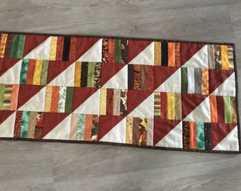 Table runner for fall, pieced strips paired with 1/2 sq. Triangles. Measures 16 1/2 x 36 1/2 inches.
